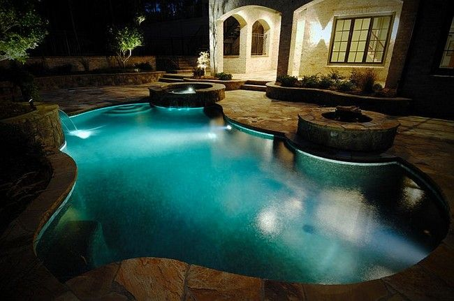 ingenious landscape lighting around pool. Ingenious pool with twin water features and a fire pit Small Pool Ideas That Will Transform Your Backyard Hangouts for
