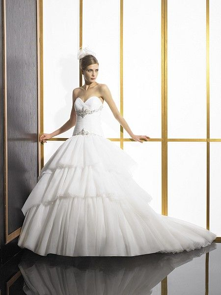 Bridal, Fall 2012. This organza and tulle ball gown features soft layers and a sweet semi cathedral train. Beading and silver embroidery accent the bodice and drop waist. #ValStefani #Bridal