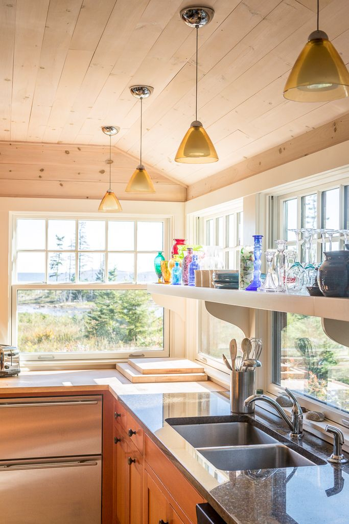 Kitchen With Knotty Pine Shiplap Walls, Polished Granite Countertops,  Cherry Cabinets, And Colorful Bottles And Glass Pendants