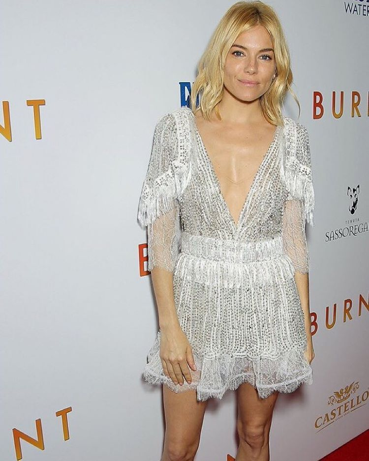 """Sienna Miller wears Rodarte's Hand Beaded White Lace and Fringe Dress to the premiere of @burnt_movie (styled by @kystyle)."""