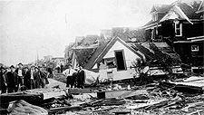 Photo d'une rue à Regina montrant des maisons détruites et des débris laissés par la tornade, 1912