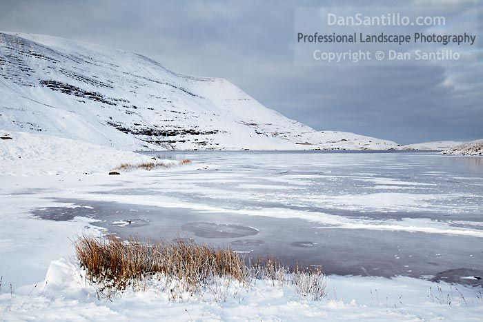 "Llyn y Fan Fawr by Dan Santillo. ""Walking to Llyn y Fan Fawr when it snows has to be done. On this occasion, the weather wasn't great and this photo was taken during a very brief spell of sun. The sun has lit up the landscape just a little bit, giving it far more depth."""