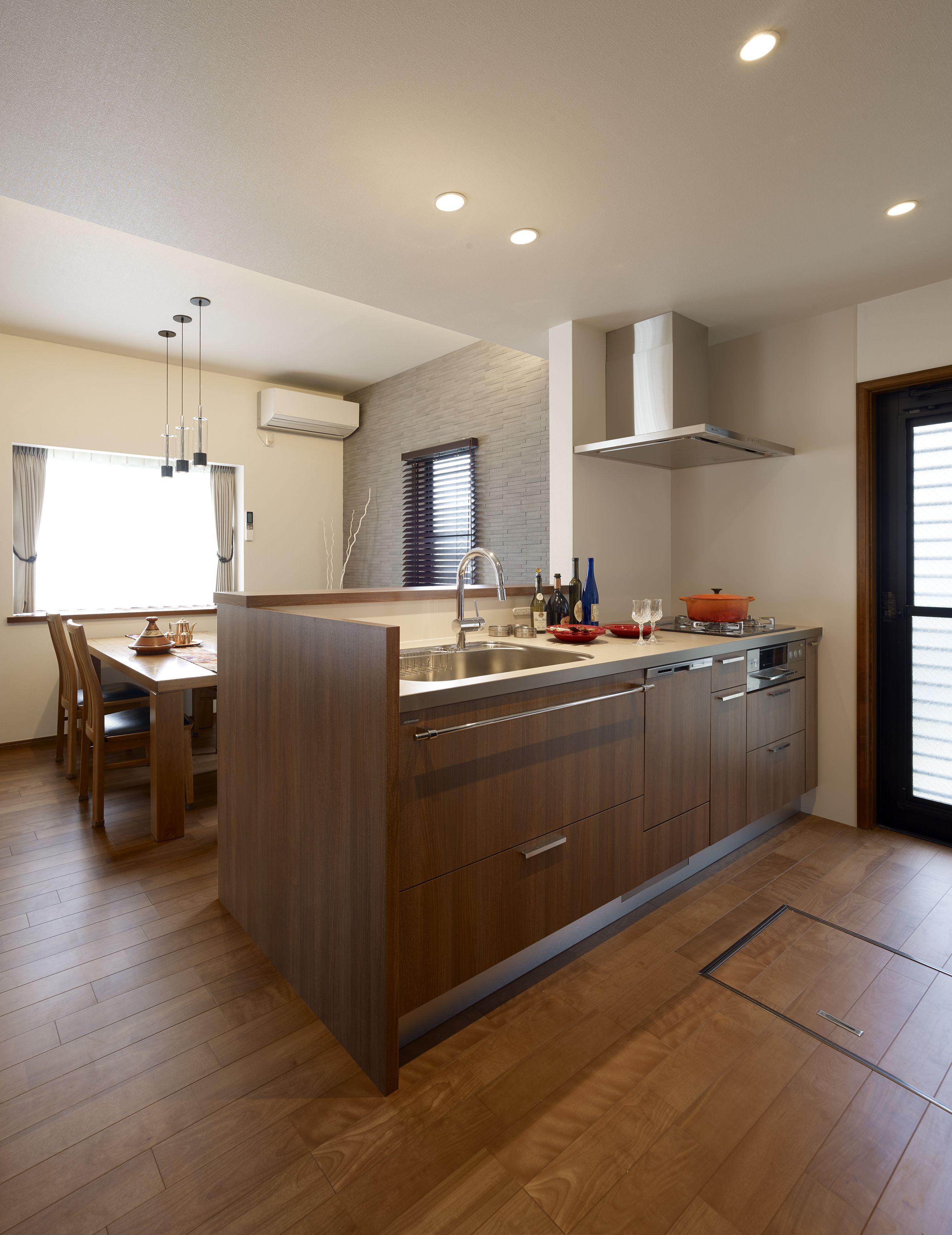 ミサワホームイングデザインリフォーム 戸建のダイニングキッチンのリフォーム 対面式にレイアウトしたキッチンは美しい木目調のキャビネットがまるで家具の様です ダイニングのフォーカルポイントにはエコカラットを貼って 木製ブラインドを掛けました ウッディな