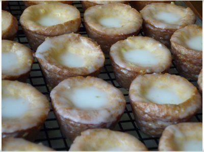 Glazed Lemon Blossoms  ---------  Tiny cupcakes are made with cake mix, pudding mix, eggs, and oil, baked, and then dipped in a tangy lemon glaze.