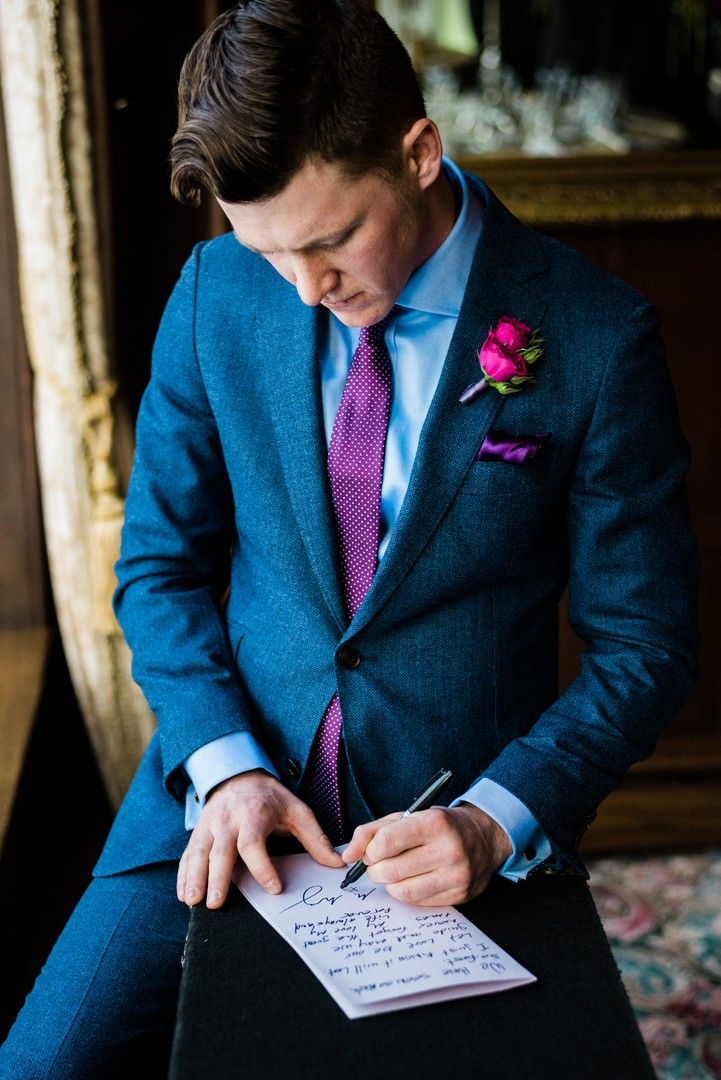 Groom in blue suit with purple tie writing special letter to his ...
