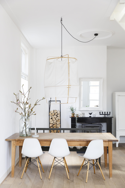 Lichte eetkamer met houten tafel en witte stoelen