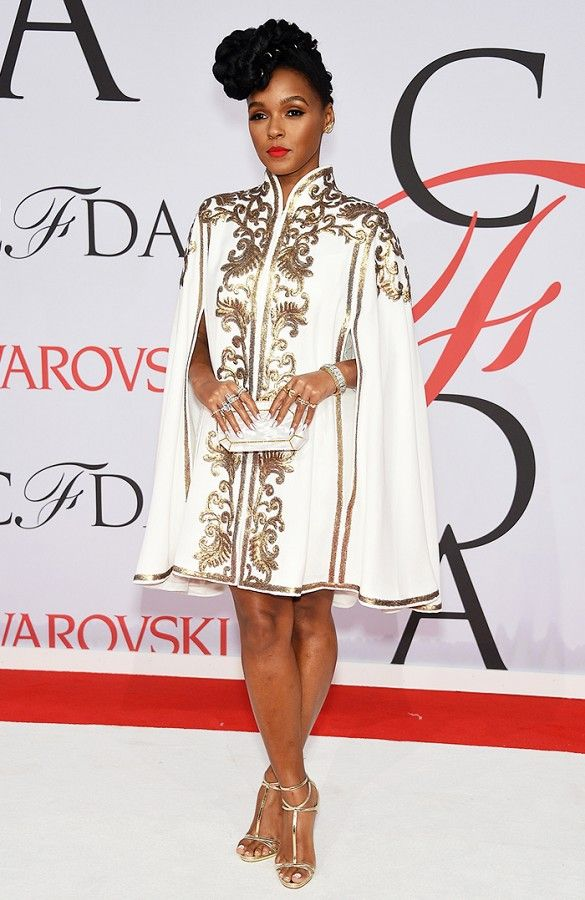 Janelle Monae in a white and gold embellished cape dress and Edie Parker clutch