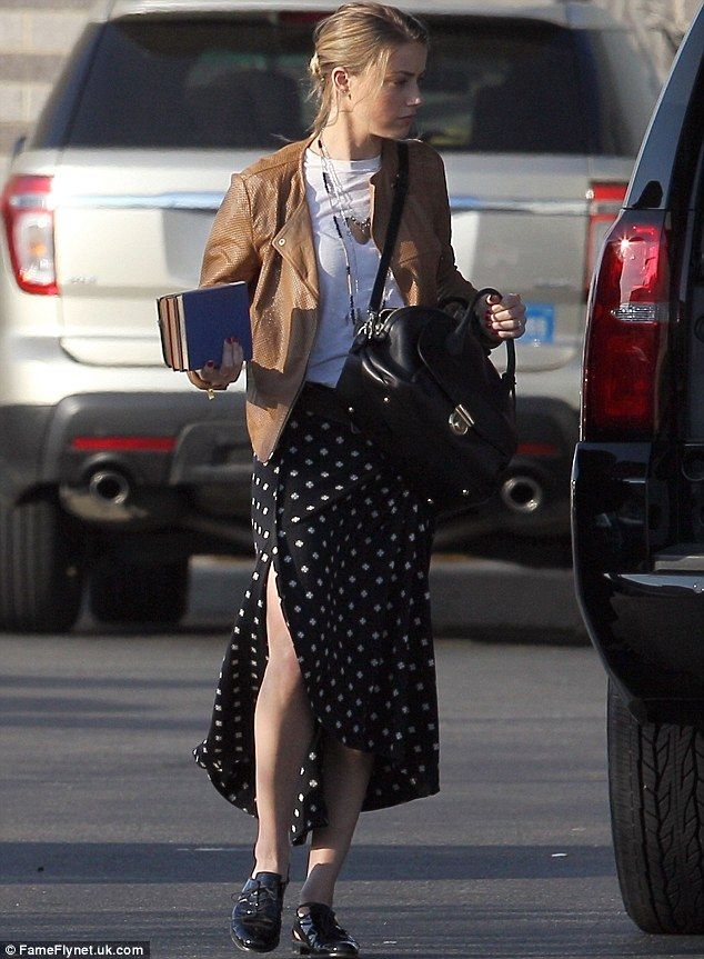 Casual chic: Amber also wore a brown leather jacket but teamed it with a white top, polka dot midi skirt, and black patent leather loafers