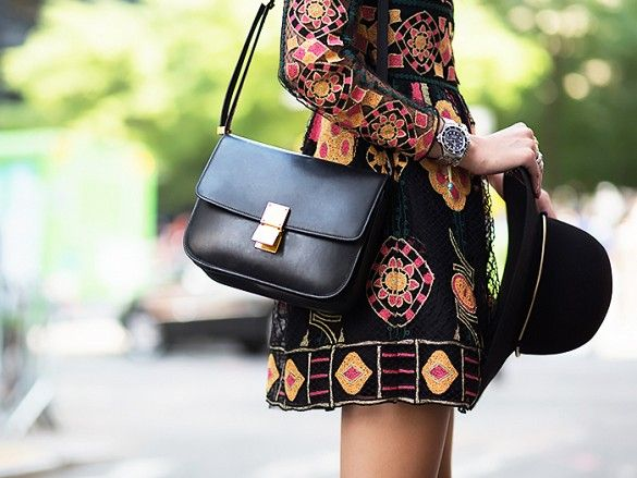 A black Celine handbag compliments a detailed dress.