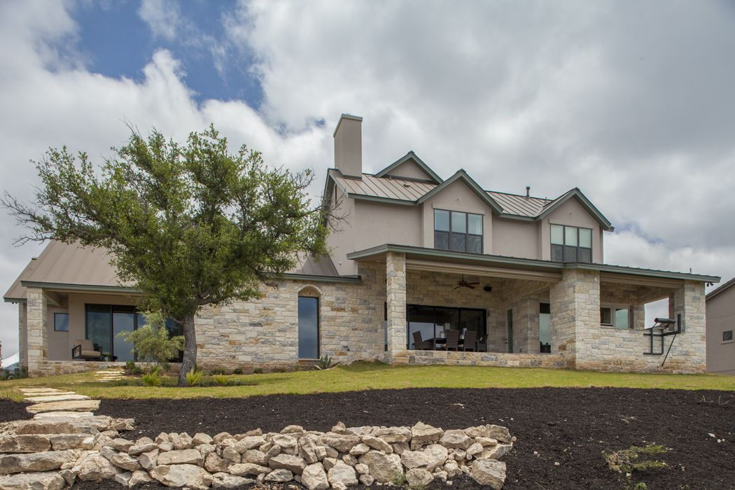 Rear elevation transitional home in the texas hill for Texas hill country stone homes
