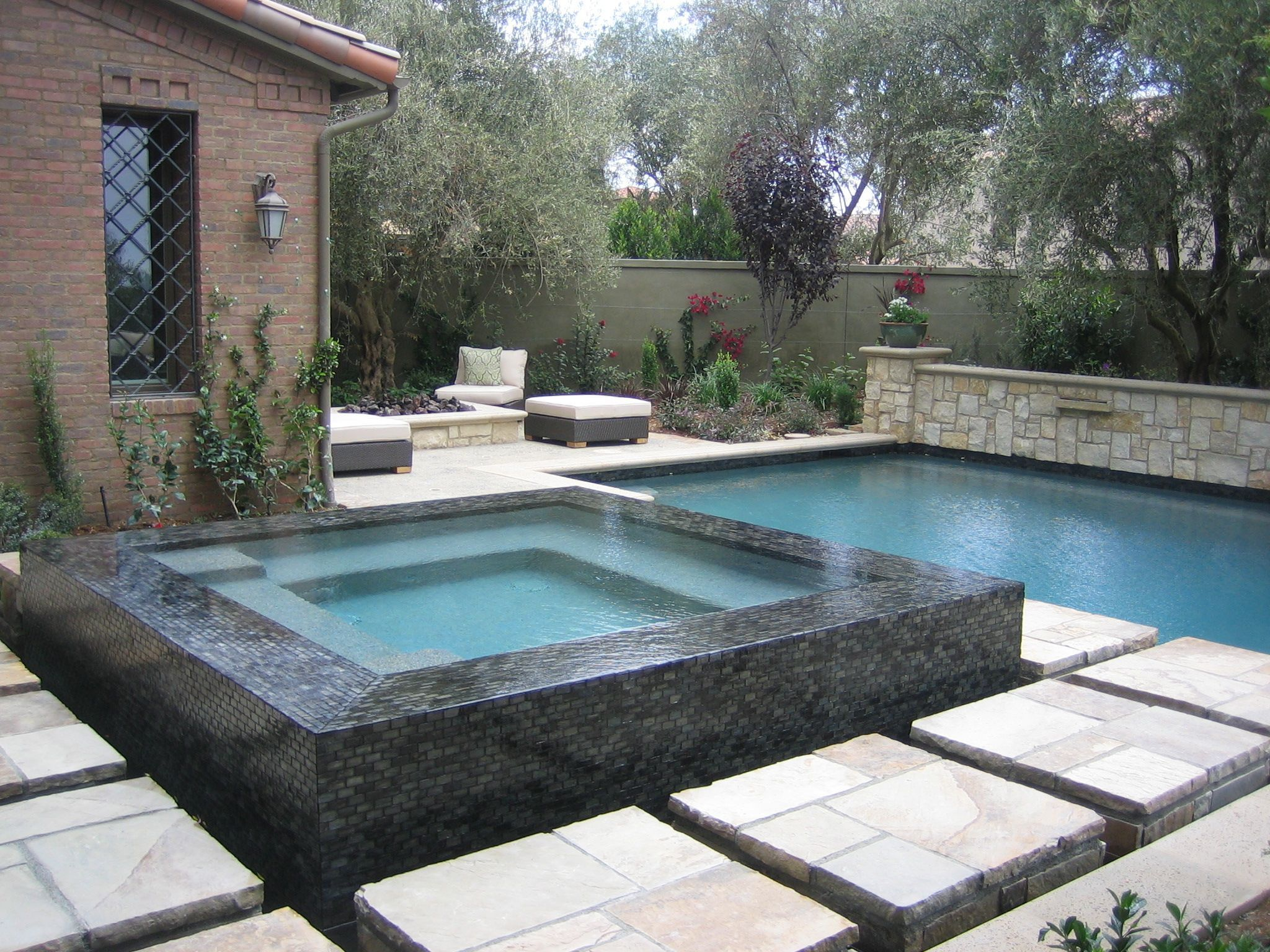 Knife edge pool 2 modern pool - Seaglass Tile Spa With Infinity Edge And Surrounded By Stone Stepping Stones Leading To Pool
