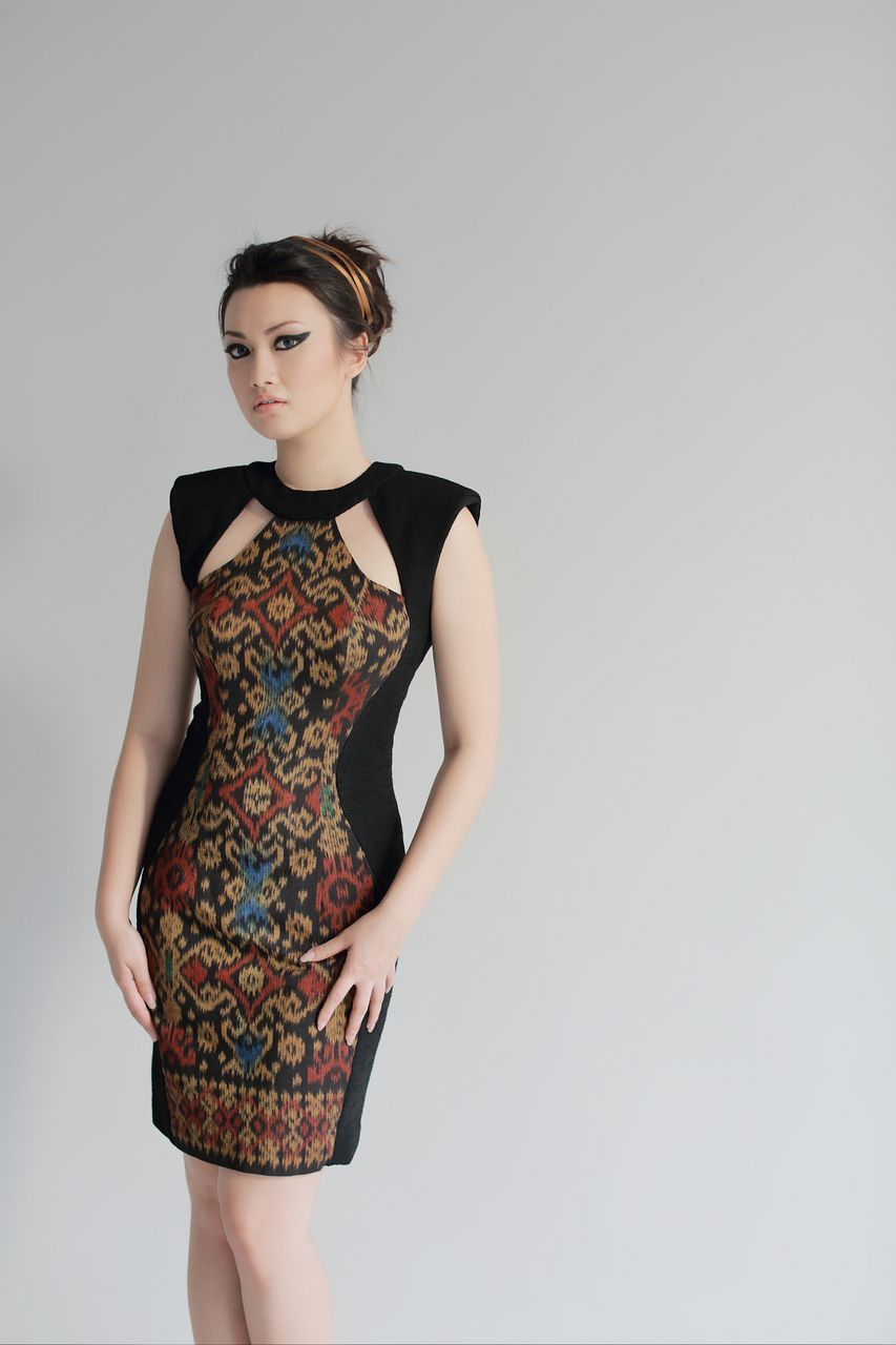 A combination of modern and traditional fabric creates a unique look to this dress. The traditional tenun ikat fabric from Jepara, combined with textured black fabric. This dress has sleeveless design, high round neck, low back cut with hook and zipper fastening.