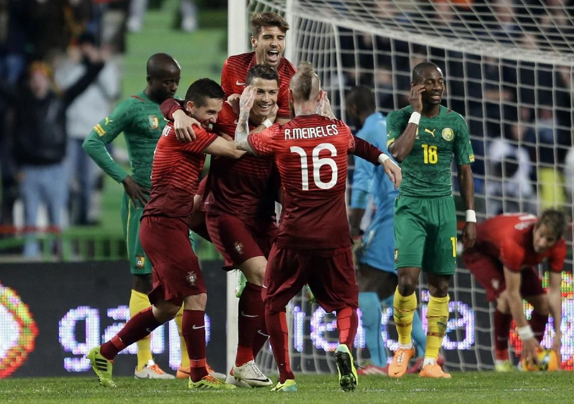 Players react after Portugal's Cristiano Ronaldo, centre scored his second goal during their friendly soccer match with Cameroon Wednesday, March 5 2014, in Leiria, Portugal. The game is part of both teams' preparation for the World Cup in Brazil