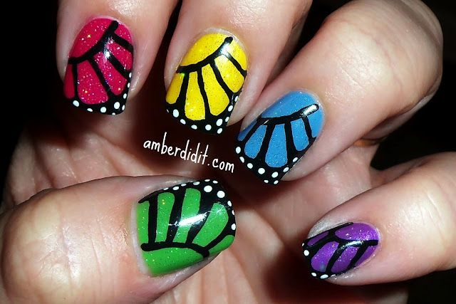rainbow butterfly manicure: rainbow skittles base, then glitter then freehand striper black, then white dots