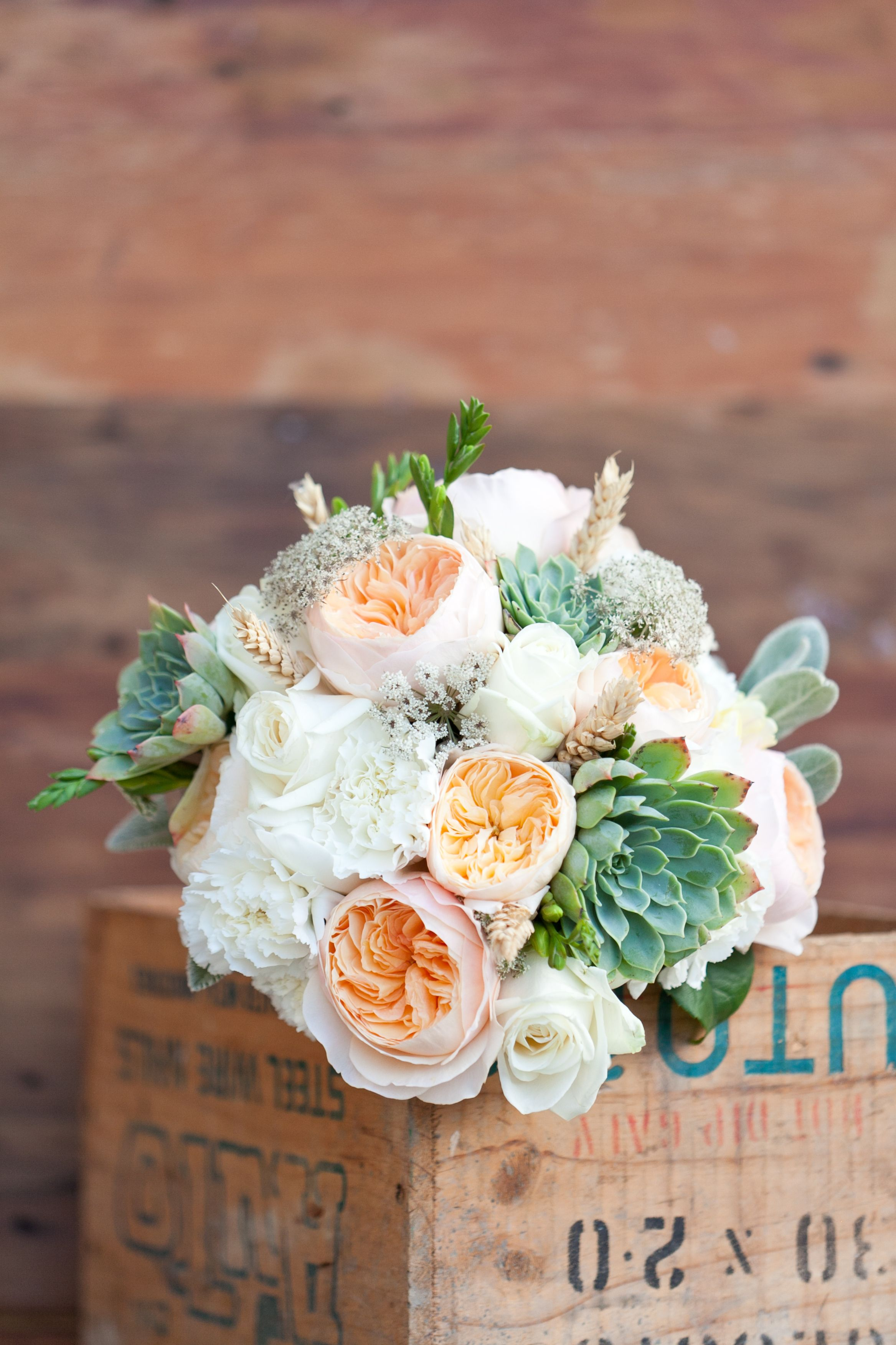 the bridal bouquet will be a clutch of cream hydrangeas peachy juliet garden roses pale green succulents ivory spray roses and grey dusty miller