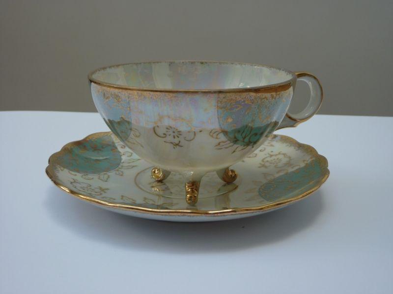 2 antieke kop en schotels gemaakt van lusterporselein. Te dateren rond 1900. De kopjes staan op 3 vergulde pootjes. Het porselein is handbeschilderd met mintgroen en goud. In perfecte conditie, geen beschadigingen of restauraties.