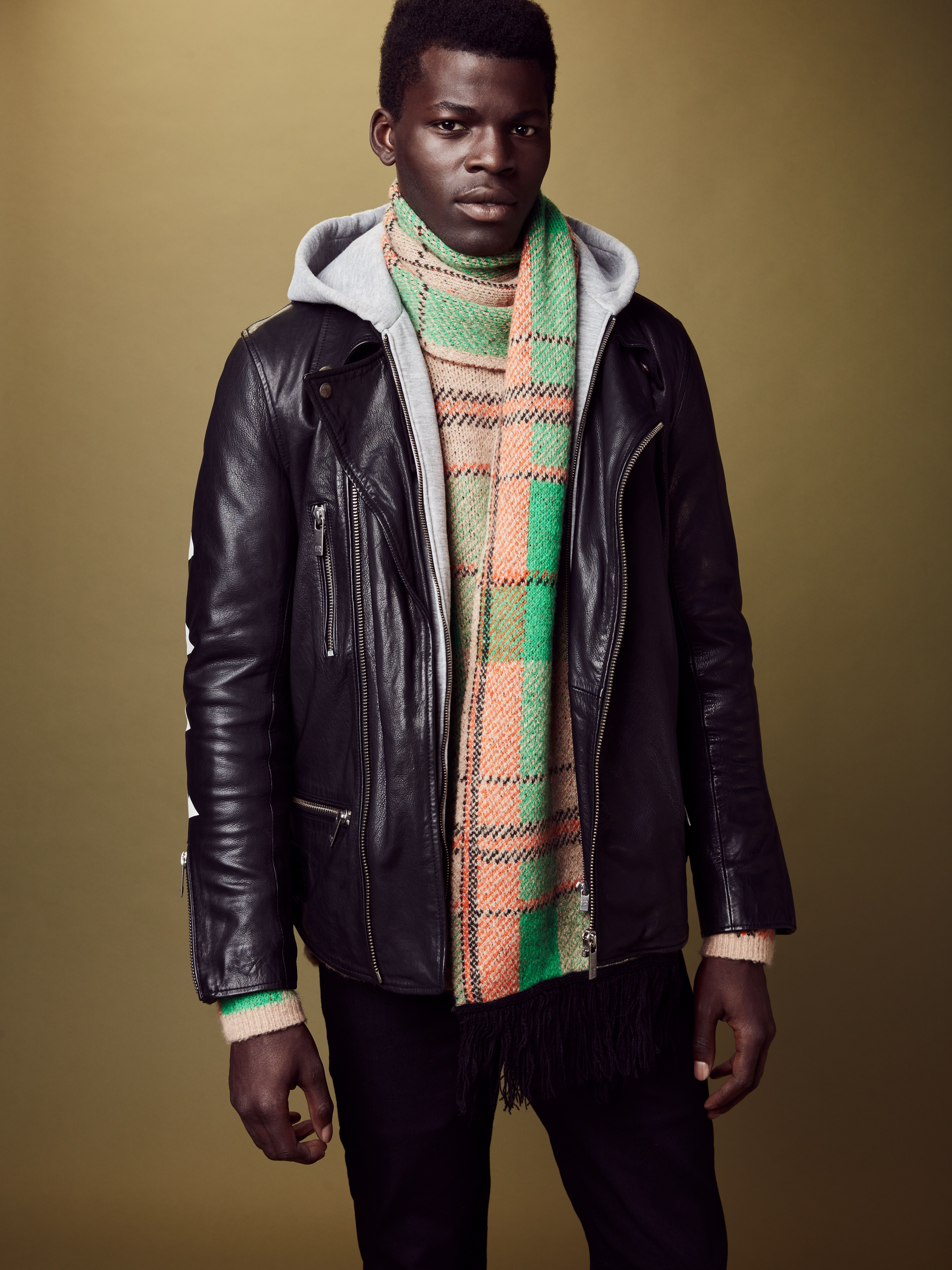 A black leather biker jacket layered with chunky knit checked pullover,  Scotch & Soda Fall-Winter 2018 men's collection.