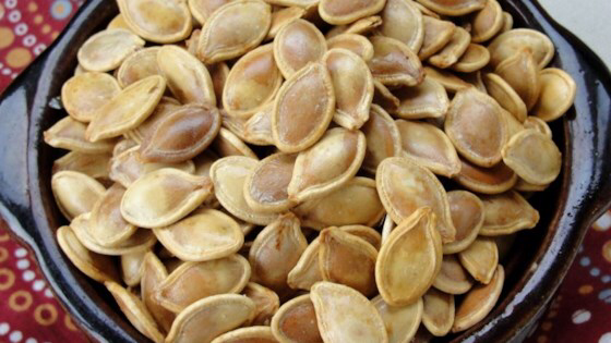 Roasted Pumpkin Seeds #roastedpumpkinseedsrecipe Fresh pumpkin seeds are roasted with butter in salt to make this popular seasonal snack. #roastedpumpkinseeds