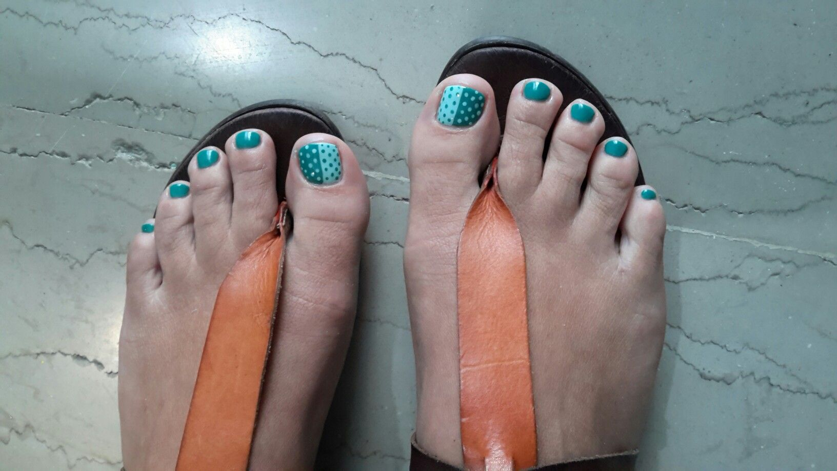 two colored pedicure of light and dark green and polka dots in