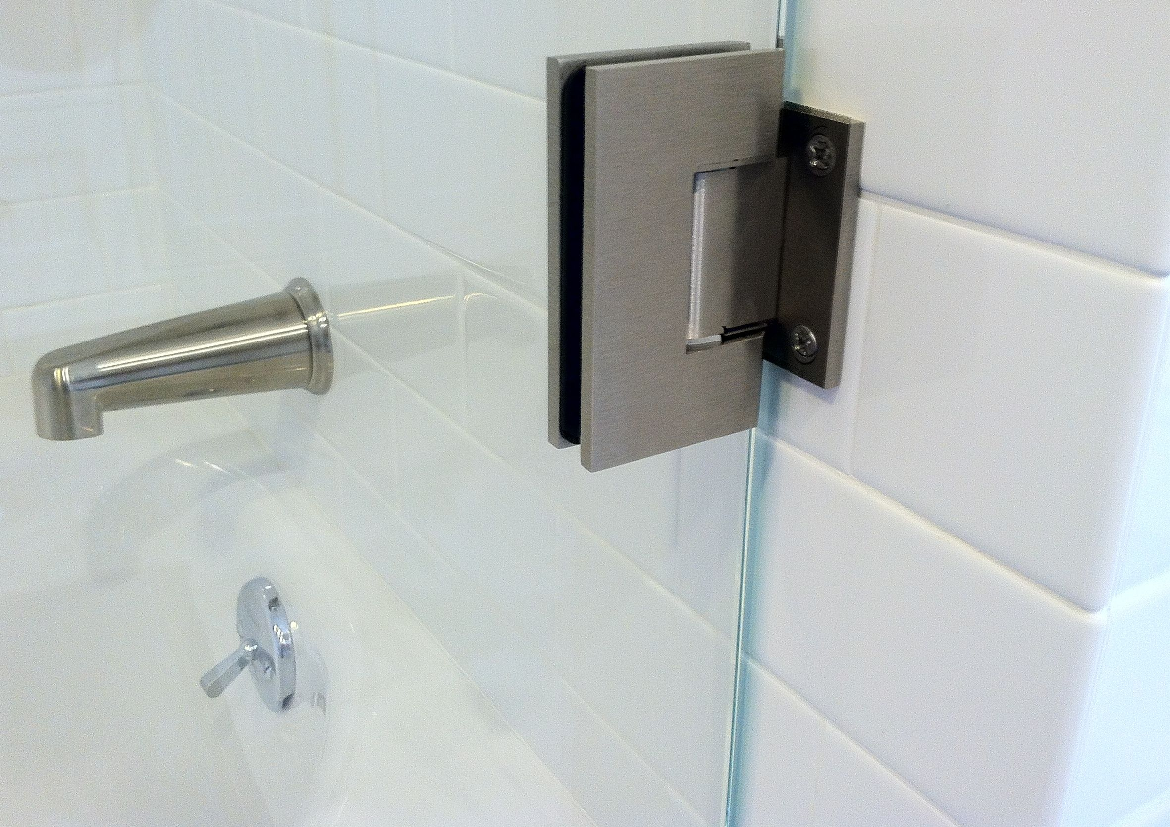 Glass To Wall Hinges Are Attached To This Tile Wall For A