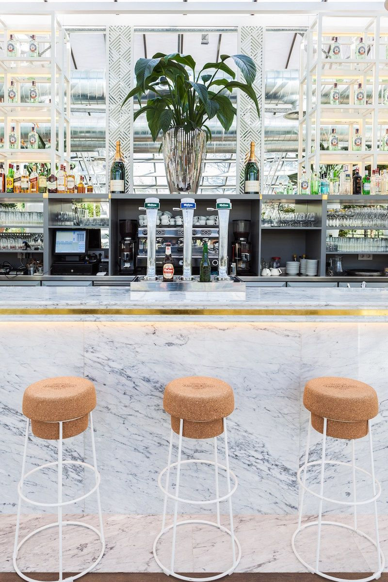 beautiful cork barstools in front of a tropical inspired bar in spain