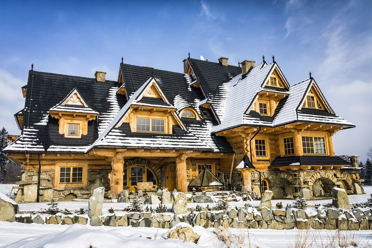 Rambling mega log home mansion with light wood logs and dark shingle roof for contrast effect snow on the ground