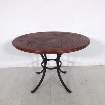 Wooden Wheel Table. - Solid wooden table top with a reddish finish- Black pedestal legs- Great condition with a distressed look