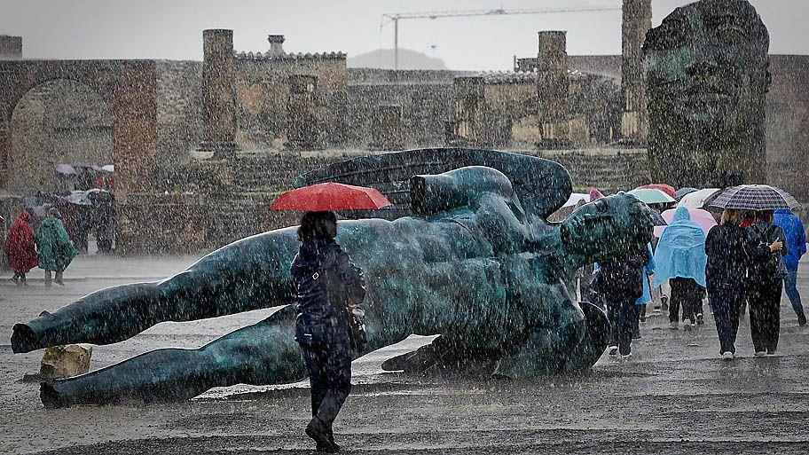 """- Visitantes enfrentam a chuva para visitar a exposição """"Mitoraj em Pompeia"""" dentro da área de escavações arqueológicas de Pompeia em Nápoles, na Itália. Foto: Ciro Fusco / EFE"""