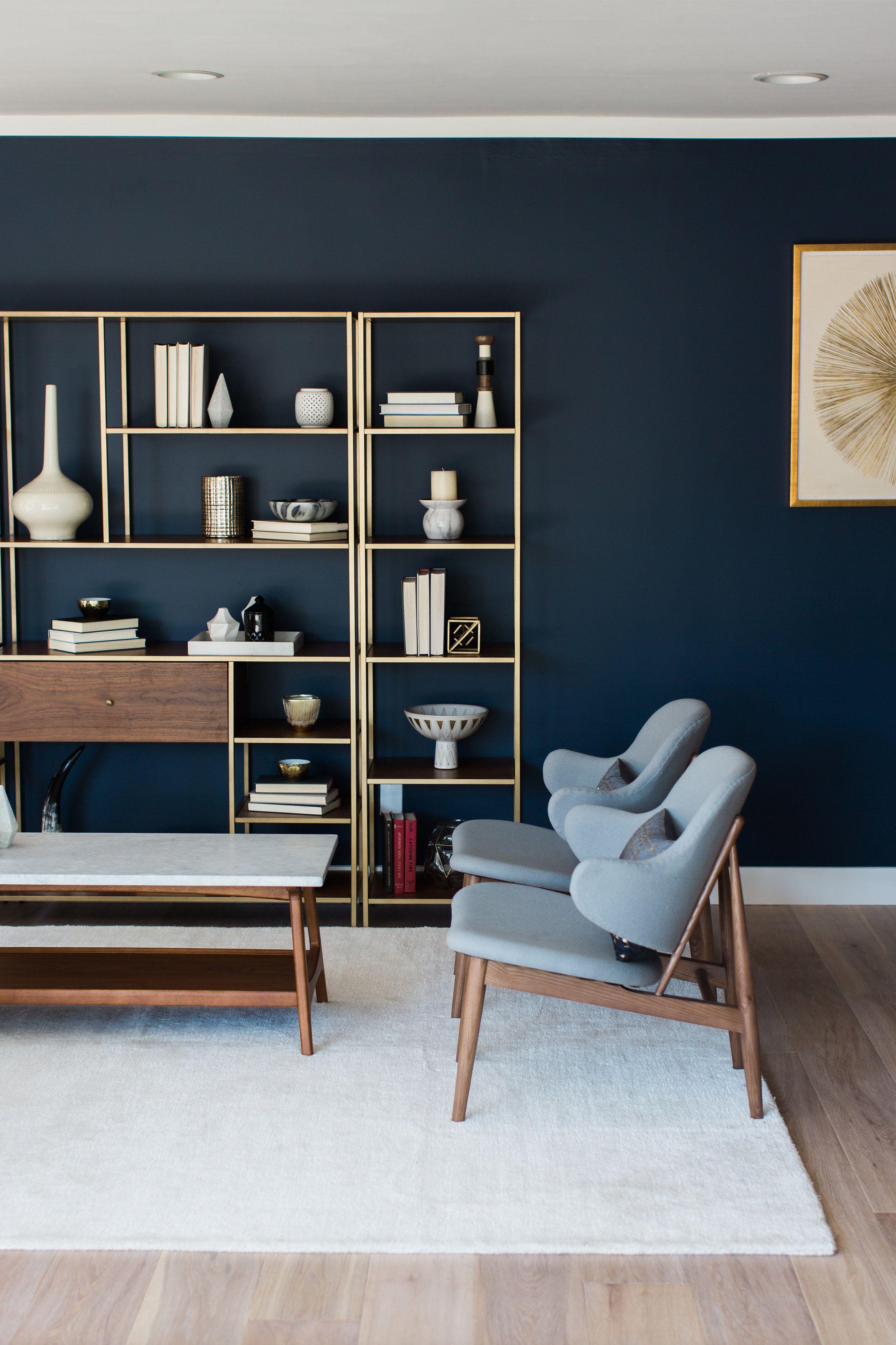 Gold Statement Bookshelves Against Dark Navy Blue Walls Lindye