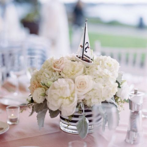 A Simple And Chic Centerpiece Of White Blooms A Striped Vase And A Small Bo In 2020 Nautical Wedding Centerpieces Nautical Theme Bridal Shower Nautical Bridal Showers