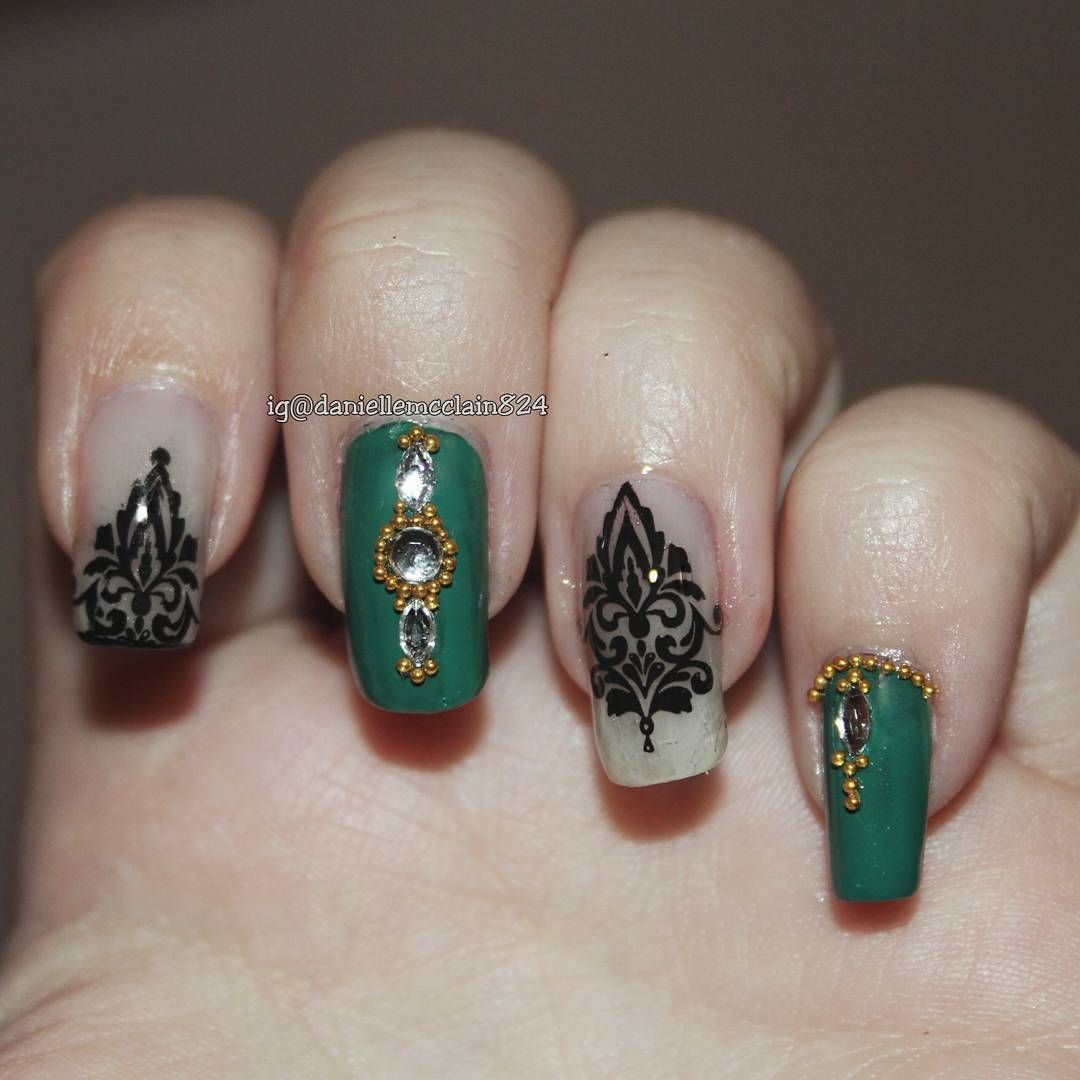 a green and gold nail art design with a damask print with ...