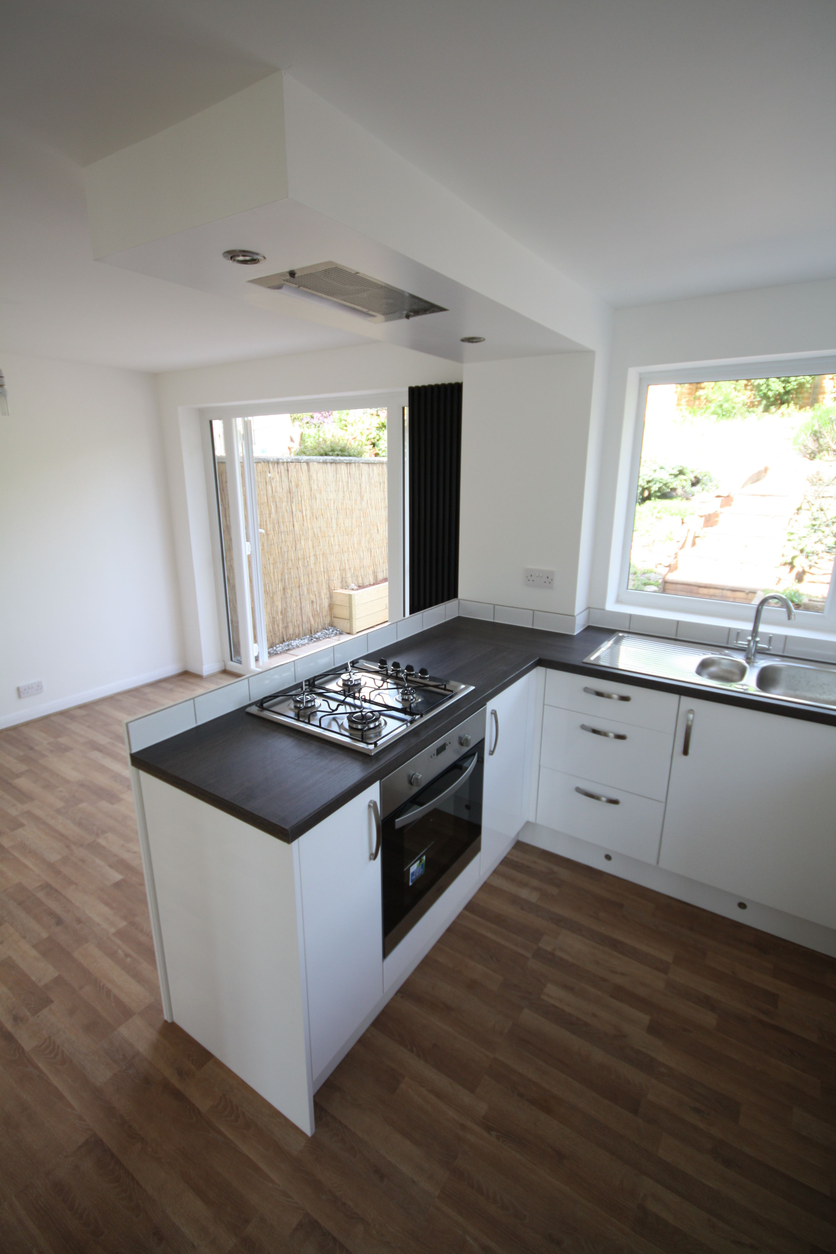 gloss white kitchen peninsular units with flush ceiling extractor