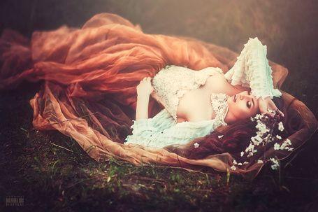 Фото Девушка в платье и с белыми цветами в руках лежит на ...