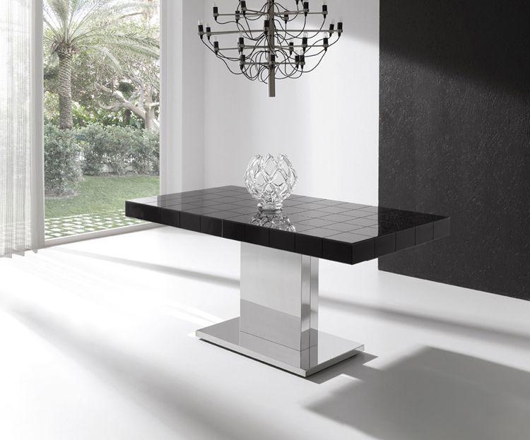 Moderna y lujosa mesa de comedor extensible. Tablero de cristal en cuadrículas.  Soporte de madera lacado y base de acero.  De 6 a 8 comensales. Acabado disponible en blanco o negro.  Medidas:   90 x 160 (extensible a 205) x 75 cm (Ancho, largo, alto) 90 x 140 (extensible a 190) x 75 cm (Ancho, largo, alto)