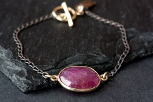"*October is Breast Cancer Awareness Month*  50% of all proceeds go to benefit the Breast Cancer Research Foundation    simple + timeless.    a natural pink sapphire is bezel set in 14kt gold and linked to oxidized, sterling silver chain.    sapphire measures approximately 15 x 12mm, bracelet measures 7""  $110.00"