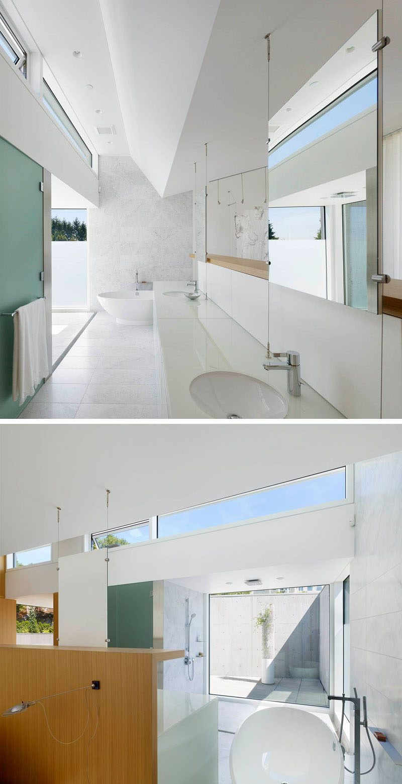 This bright white bathroom has hanging mirrors, touches of wood, and lots of natural light from the floor to ceiling window in the shower.