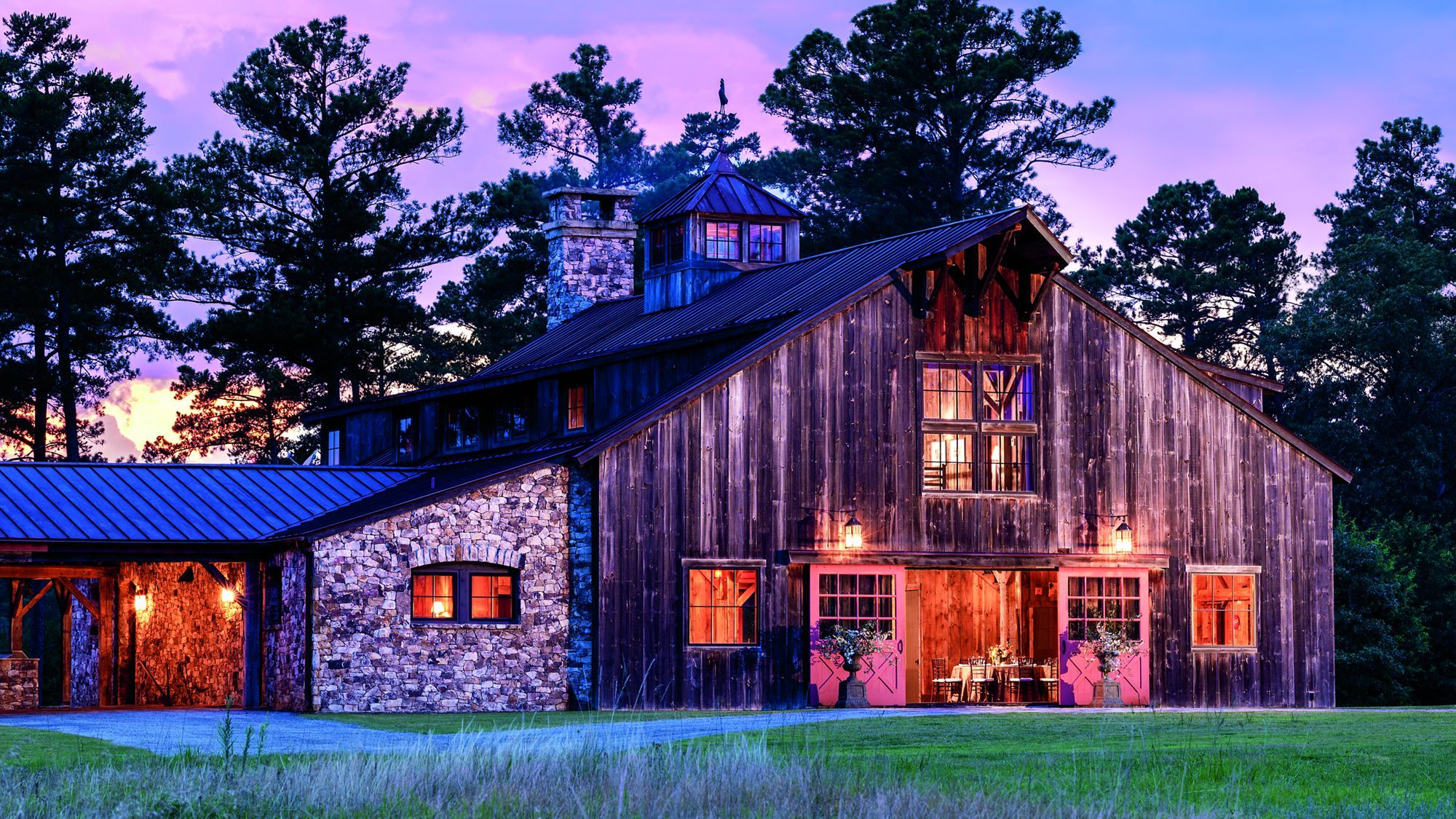 Exterior of a barn at dusk with trees in the background ...