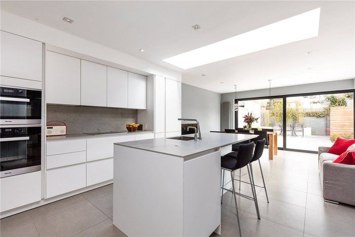 bright and white siematic by arena kitchens with a skylight above