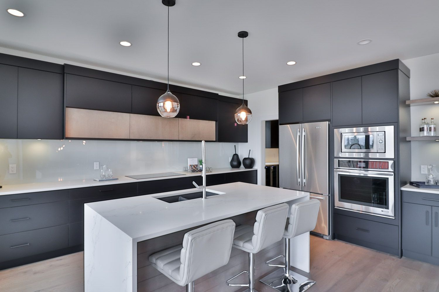 Black and glass contemporary pendants over the kitchen ...
