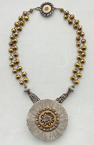 Necklace   Leslie Lawton.  A Victorian Celluloid button is set off by an etched sterling pattern, also Victorian. Then strung with gold freshwater pearls.