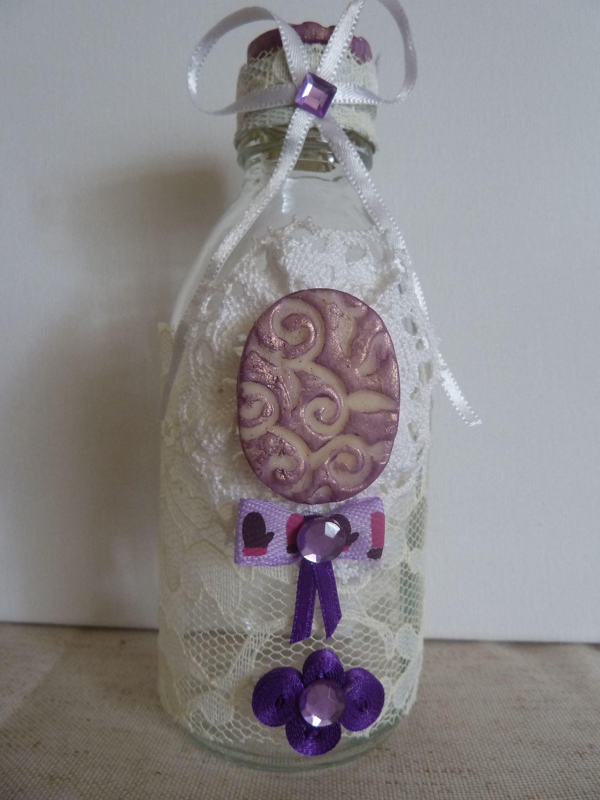 Bouteille romantique en verre recyclée, décorée de dentelle fine écrue, d'un cabochon en porcelaine froide travaillé et peint, de cabochons violets en tissu, d'un noeud en satin, de strass.