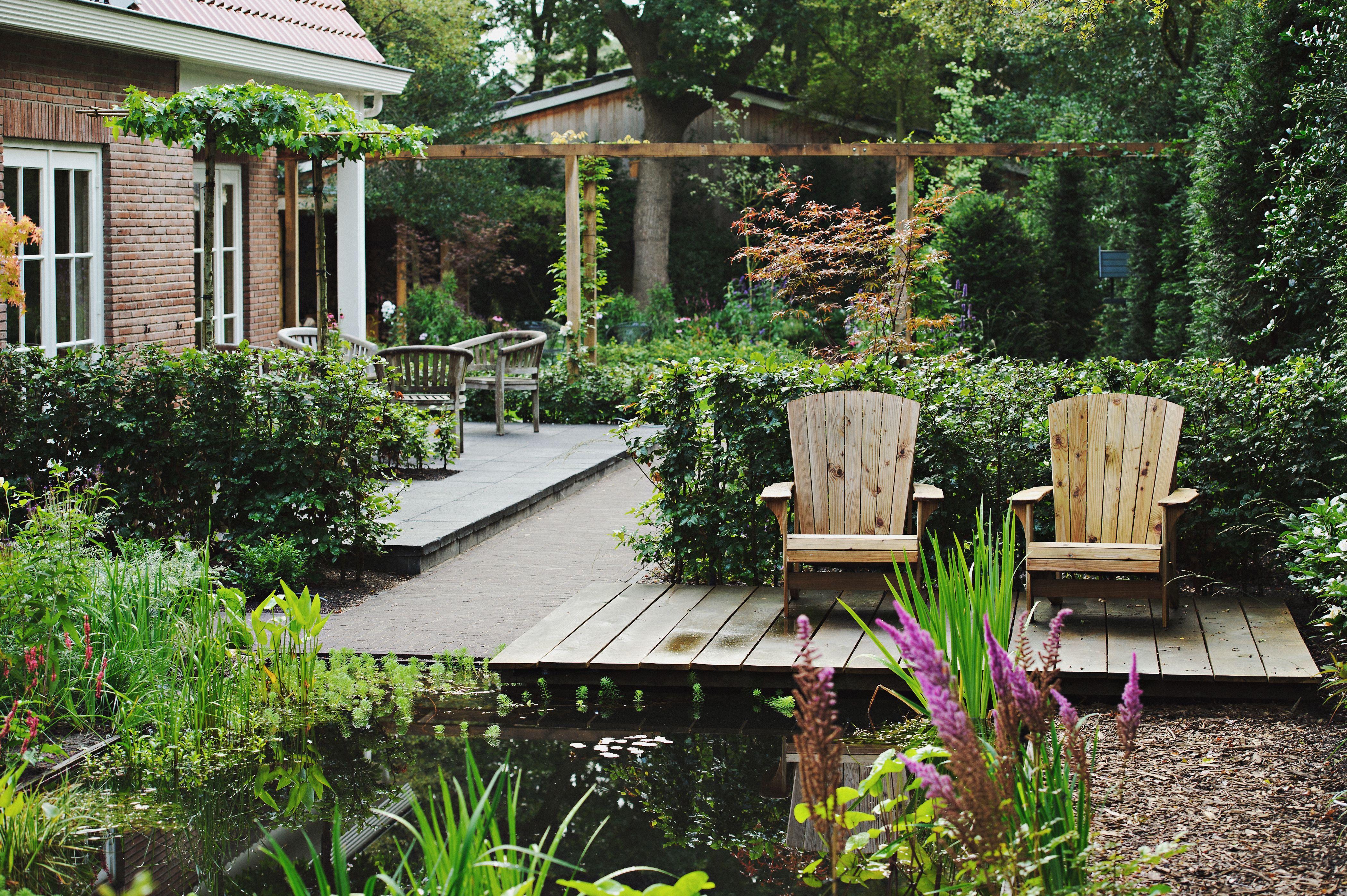 Modern klassieke tuin. vlonder met luie stoelen aan de vijver