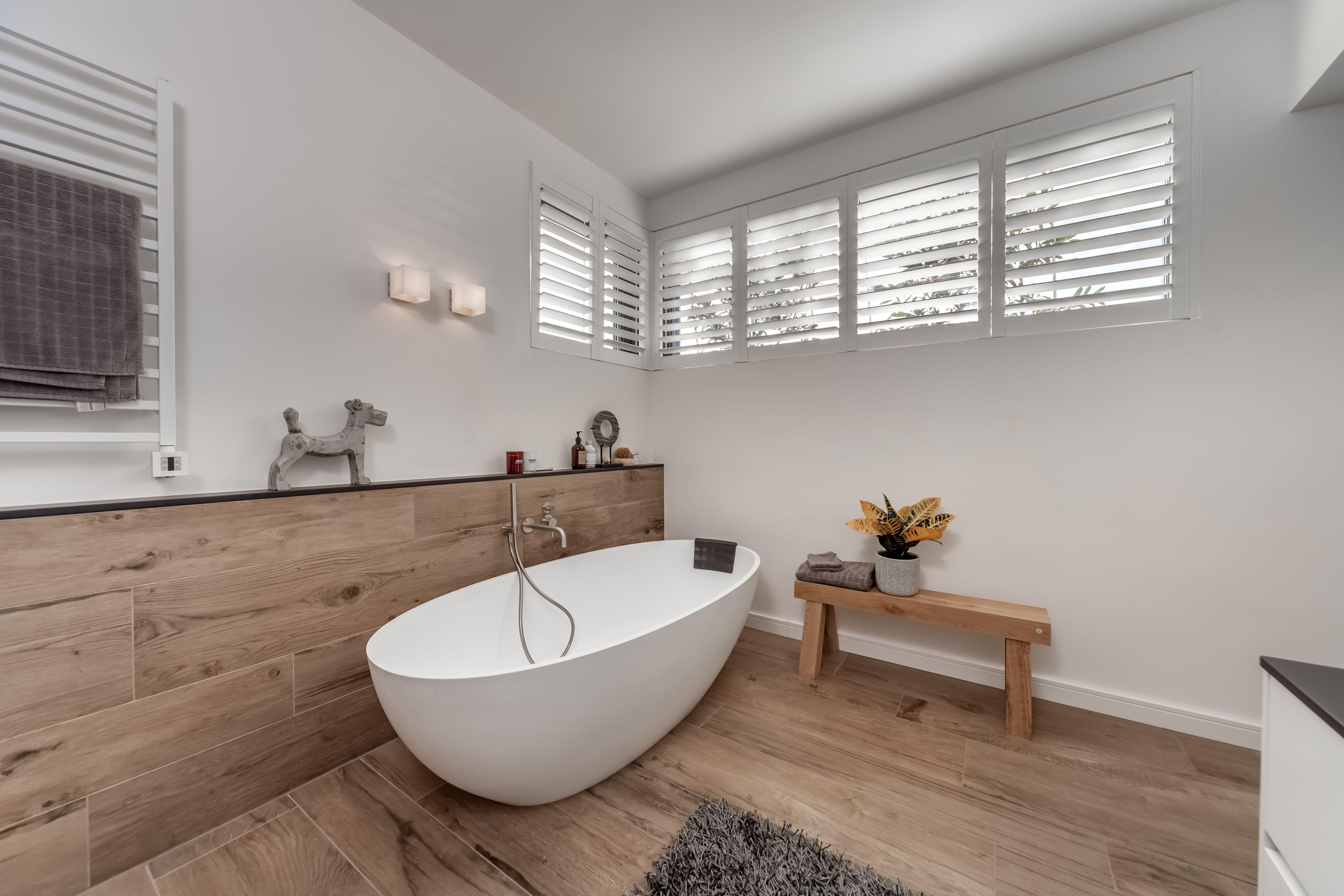 Witte shutters in een hoog raam van prachtige badkamer met