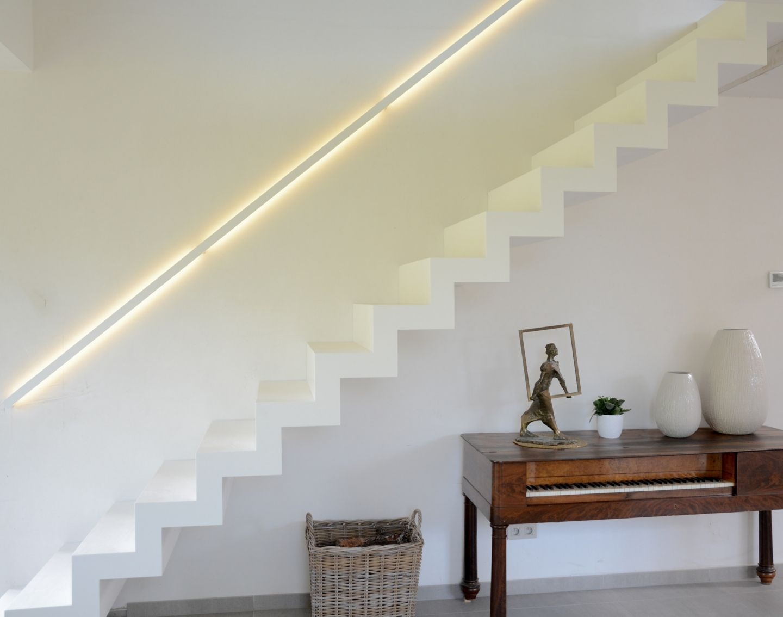 Moderne witte trap in Corian met leuning langs de muur met ...