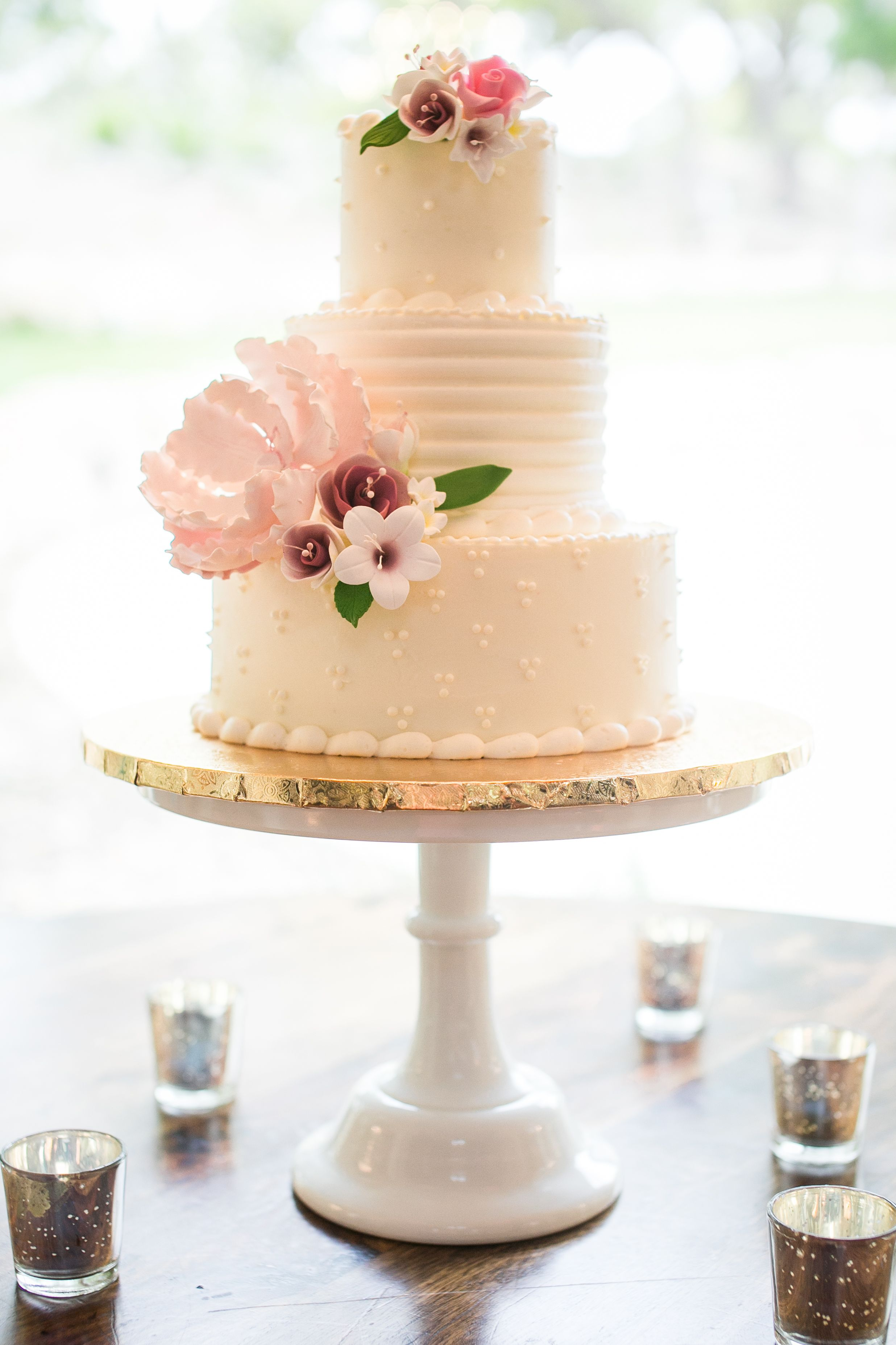 White buttercream wedding cake with sugar flowers cakes