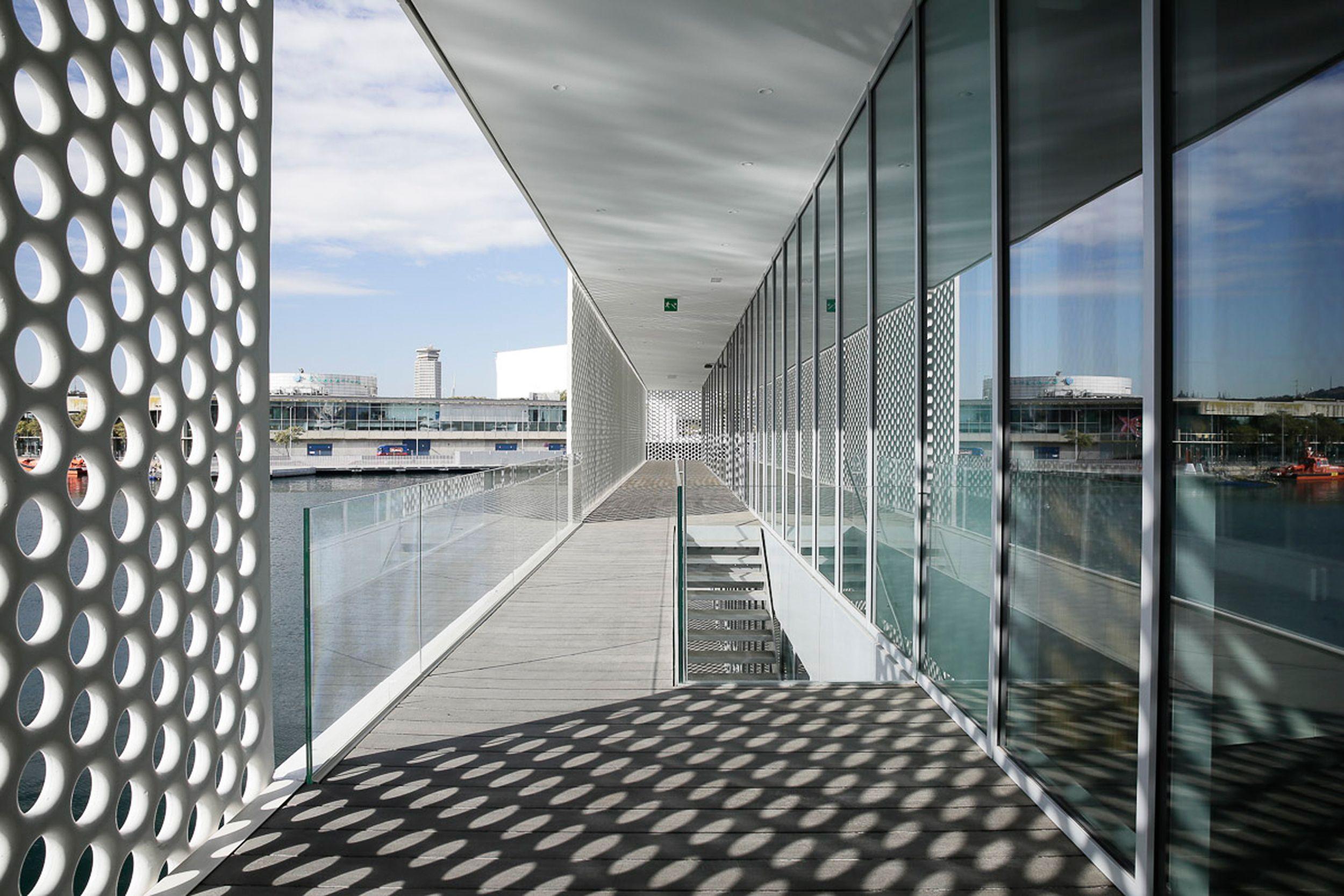 Filigree lattice screens in perforated metal make two marina buildings designed…