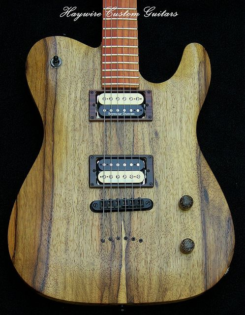 This Haywire Custom Telecaster is a solid Korina Carved top body  with a contoured heel and an arch string through body design and recessed tune-o-matic bridge. Installed are a matched set of  black and cream Seymour Duncan Pearly Gates Humbuckers wired with a push pull volume knob which splits the coils in both pickups.