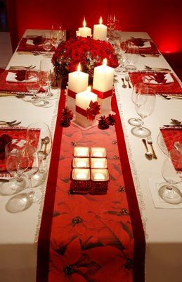 Poinsettia red runners and place mats with cream candles: Christmas elegance.