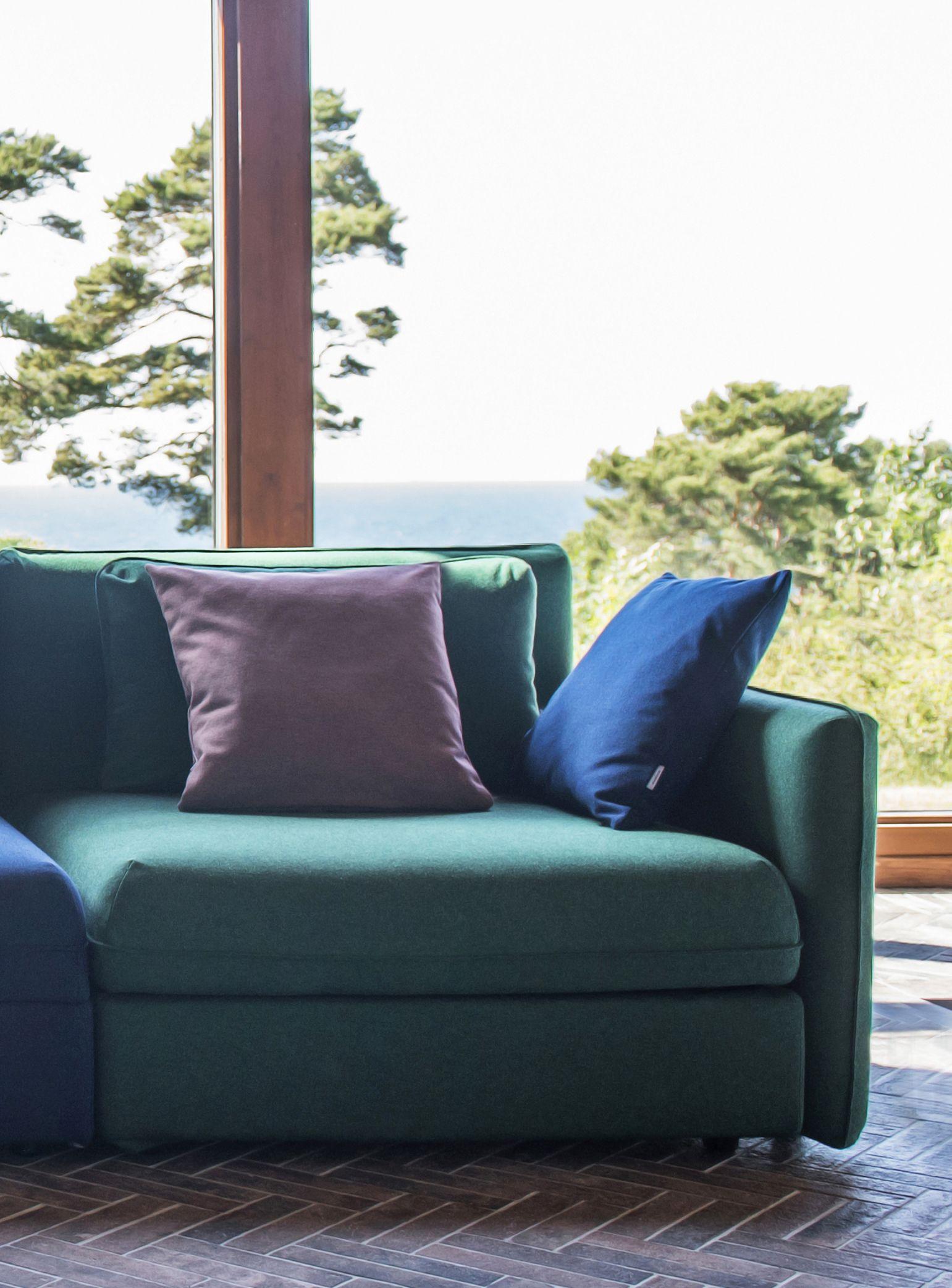 Emerald green green sofa against huge windows