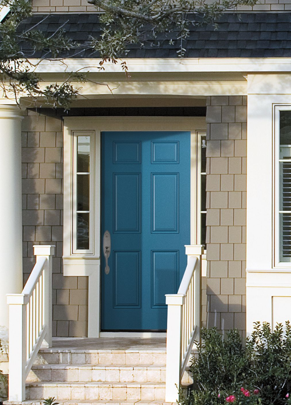 a peacock blue front door is a lively welcome to guests and